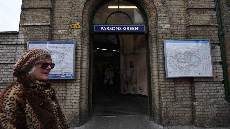 Woman walks past Parsons Green Tube station