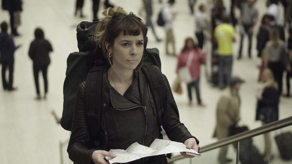 A woman holding a map in a train station
