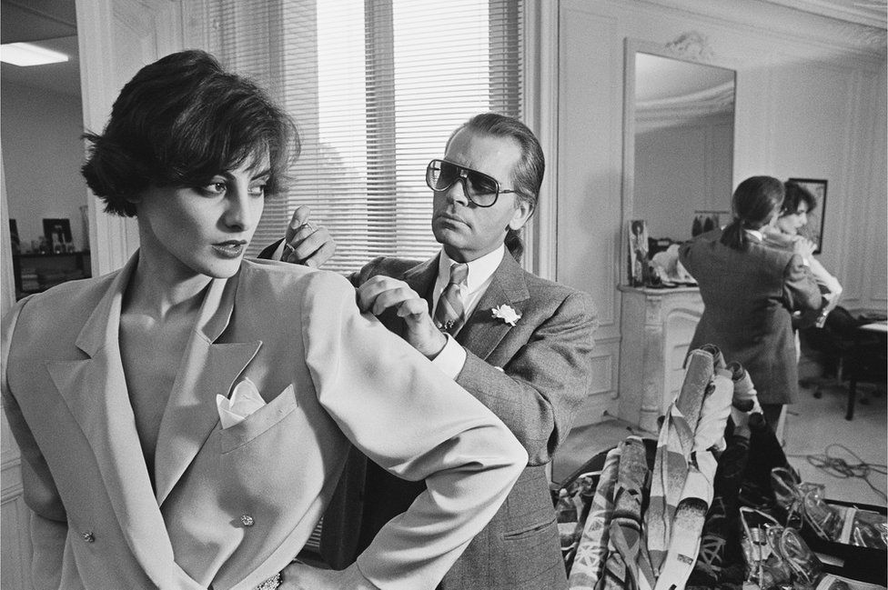 Karl Lagerfeld fits one of his designs on top model Ines de la Fressange at Chloe's Paris studio.