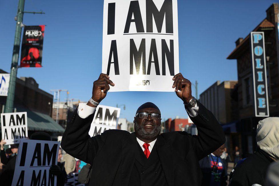 A man holds a sign declaring 'i am a man'