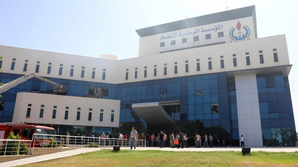 Fire trucks and people are seen near the headquarters of Libyan state oil firm National Oil Corporation (NOC)