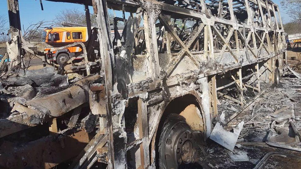 The burnt-out remains of a passenger bus that caught fire are seen near Beitbridge, Zimbabwe