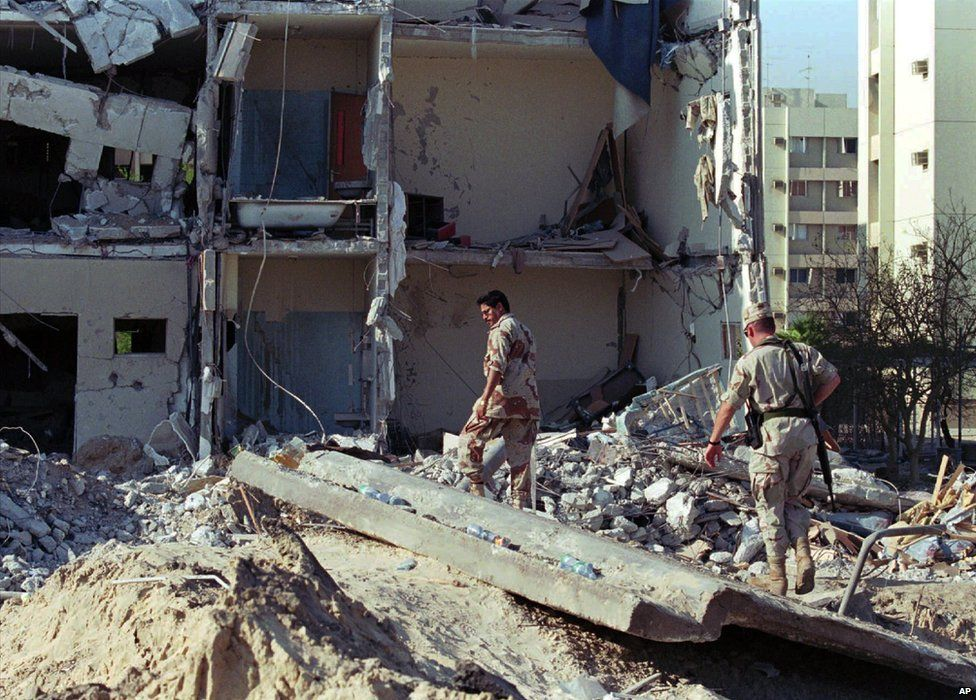 Saudi and US military personnel walk through the remains of the Khobar Towers housing complex after a bomb attack on 27 June 1996