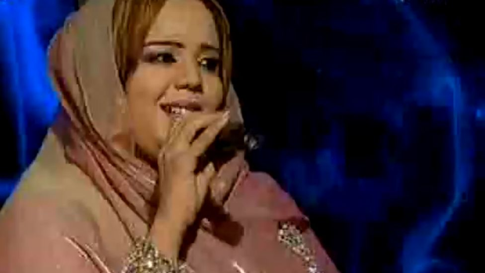 Nada Algalaa sings into a microphone as she performs on stage, wearing a pale pink dress and headscarf.