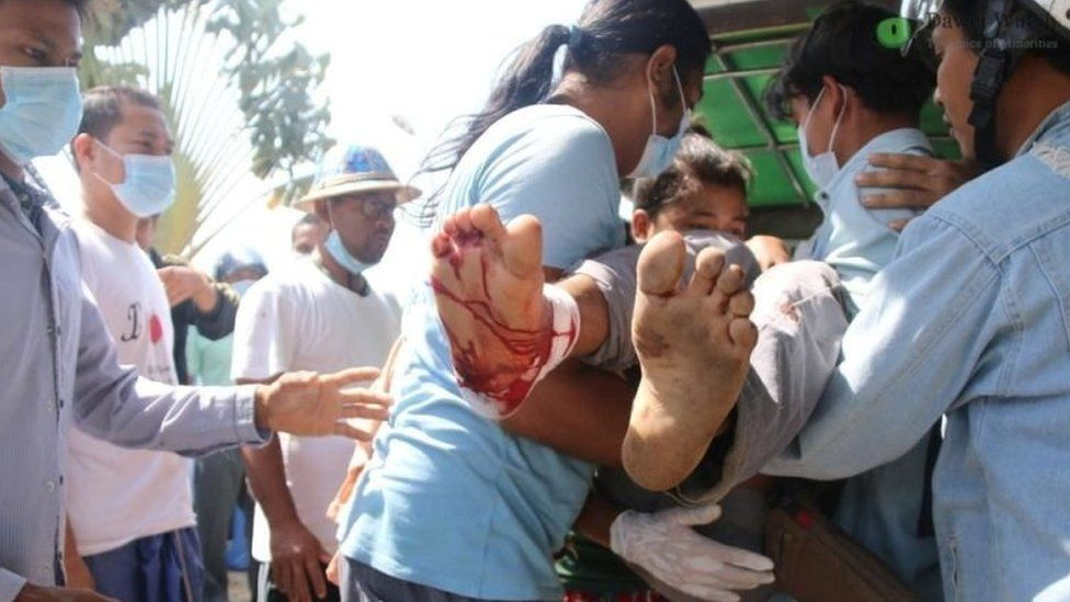 Medical staff carry away a wounded protester in Dawei