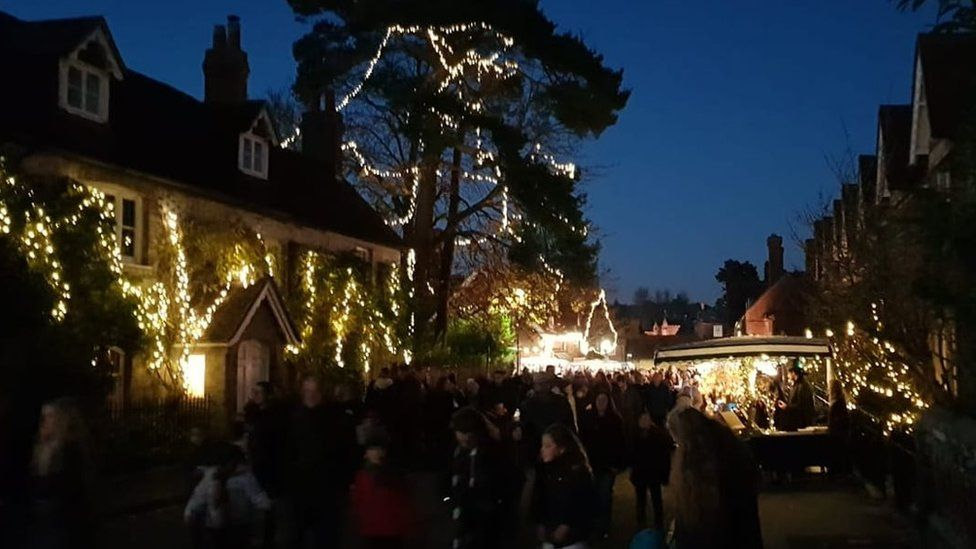 A crowd in a street illuminated by fairy lights