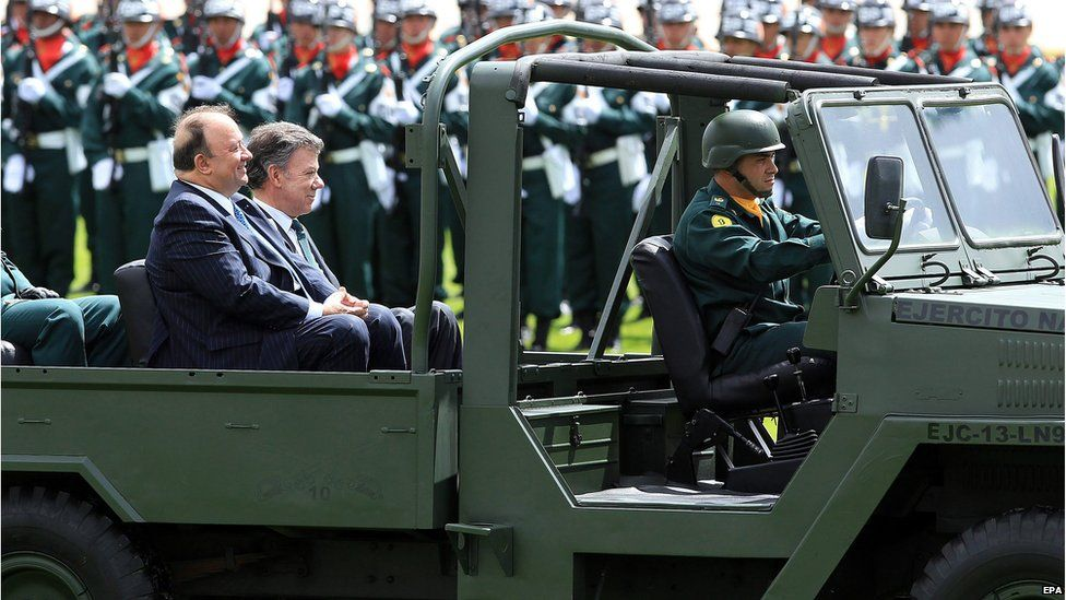 Colombia's President Juan Manuel Santos (right) sits in an army vehicle during a military ceremony in Bogota, Colombia, on 24 June 2015.