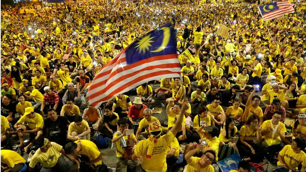 A man waves a Malaysian flag during a rally of thousands of people clad in yellow T-shirts, protesting against the prime minister on 30 August