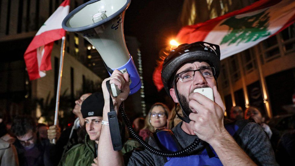 A Lebanese protester speaks into a megaphone outside the home of Saad Hariri in Beirut (16 December 2019)