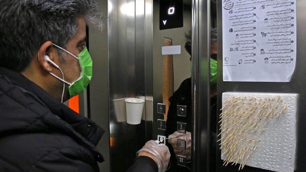 An Iranian man uses small sticks to push the elevator button at an office building in Tehran on March 4, 2020