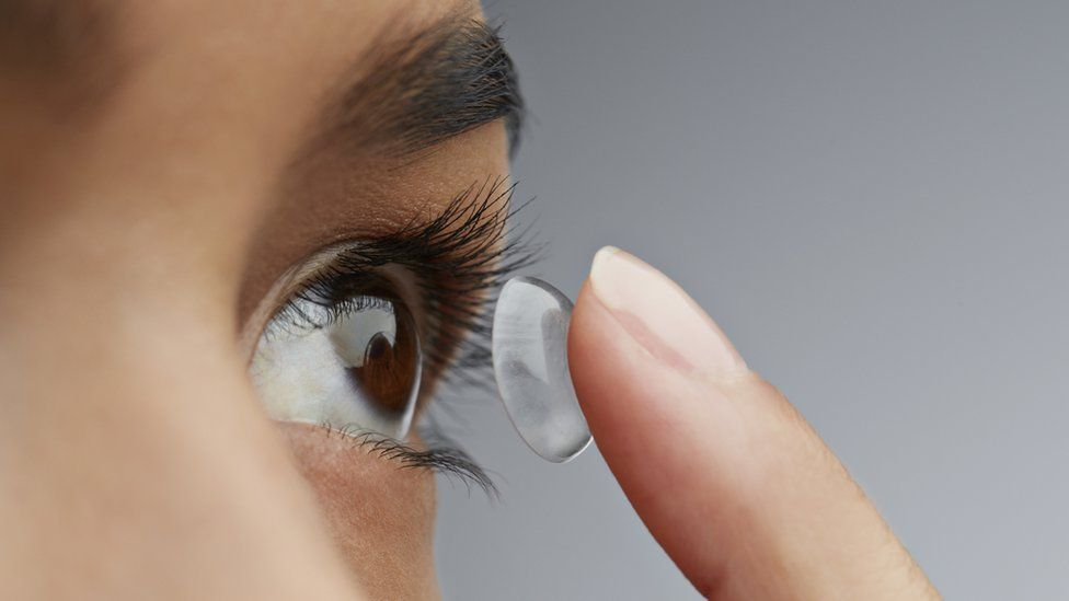 Stock image of a woman putting in a contact lens