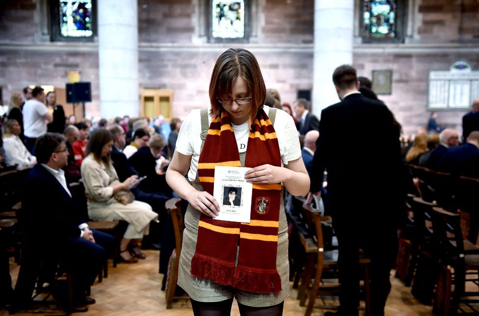 A friend of Lyra McKee holds an order of service as she attends the funeral of murdered journalist Lyra McKee