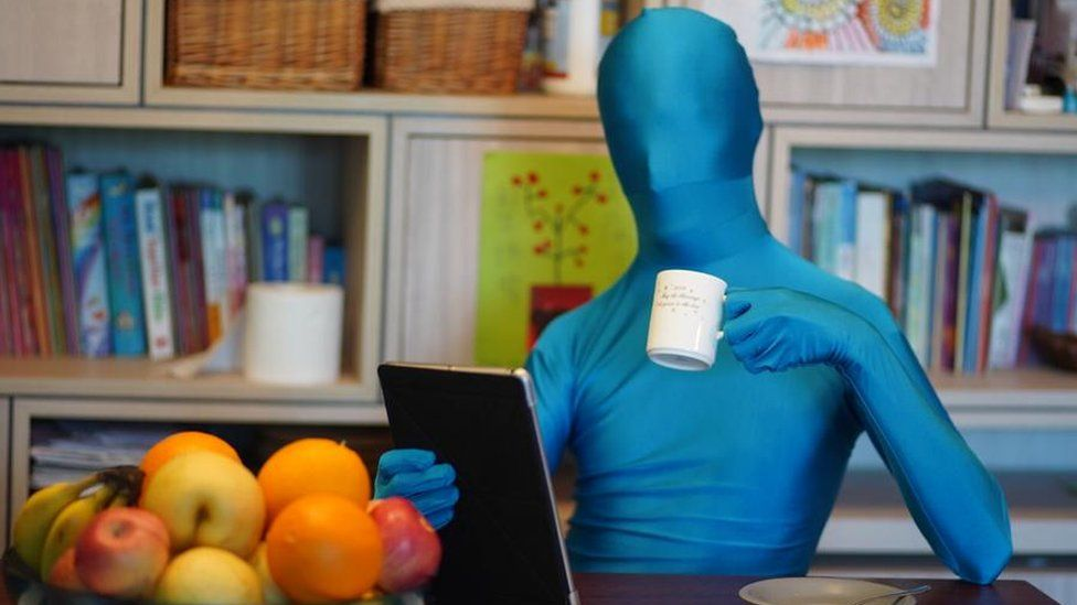 Man covered in lycra (including face) sitting at a table looking at a tablet