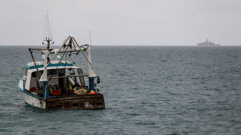 A fishing boat off the coast of Jersey with HMS Tamar in the background on the horizon