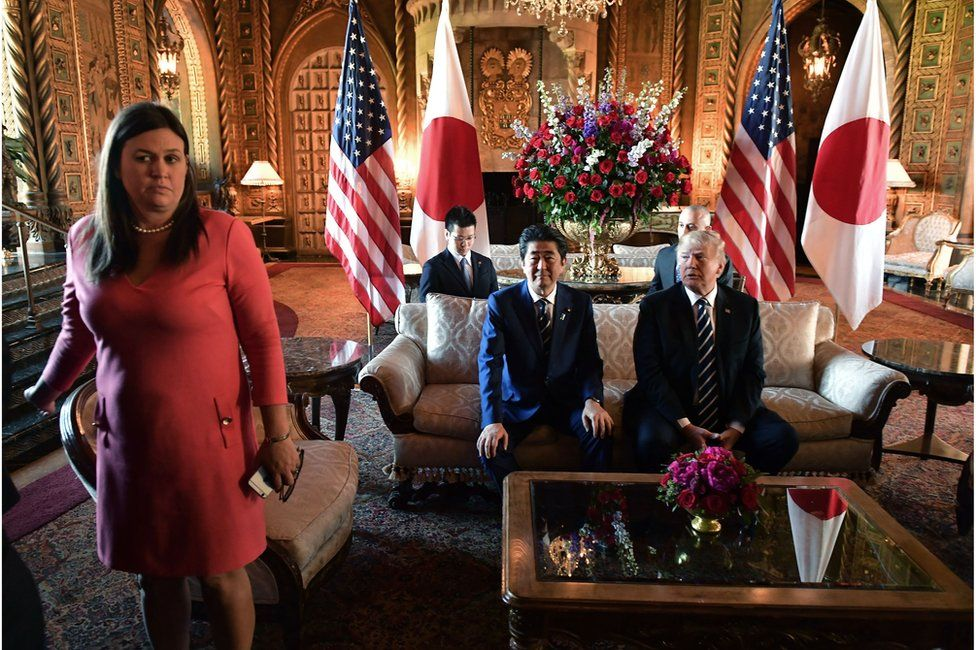 US President Donald Trump greets Japanese Prime Minister Shinzo Abe as he arrives for talks at Trump's Mar-a-Lago resort in Palm Beach, Florida, on 17 April 2018. White House Press Secretary Sarah Sanders is at left