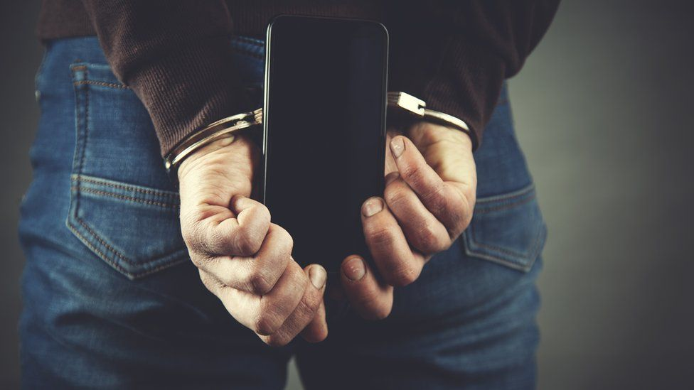 A handcuffed man holds a mobile phone behind his back