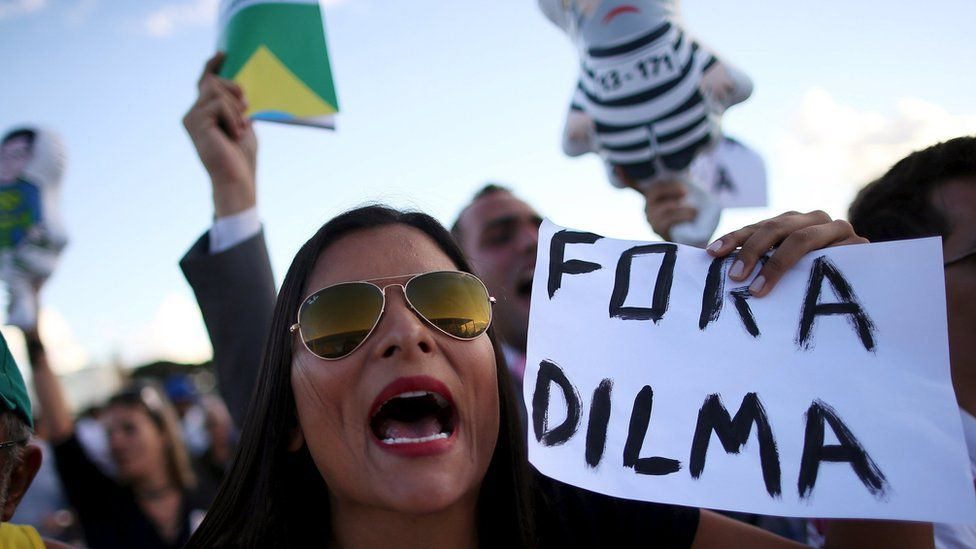 An anti-government demonstrator shouts slogans against a supporter of Brazil's President Rousseff