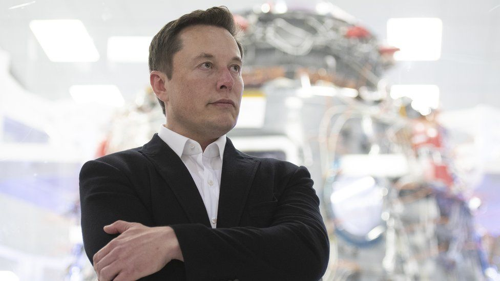Elon Musk with his arms crossed, wearing a suit
