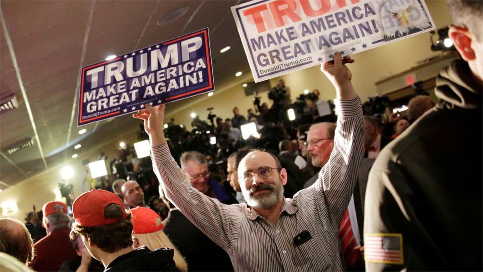 Frank Ricci, of Providence, R.I., holds signs supporting Republican presidential candidate, businessman Donald Trump while supporters wait for Trump to attend a primary night rally, Tuesday, Feb. 9, 2016,