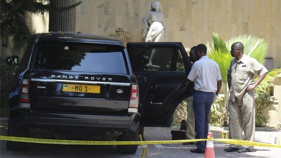 """Tanzanian police officers inspect a vehicle with registration number """"MO 1"""" that belongs to Mohammed Dewji, a Tanzanian business tycoon who is said to be Africa""""s youngest billionaire, parked at Colosseum Hotel and Fitness Club in Dar es Salaam, Tanzania, 11 October 2018."""