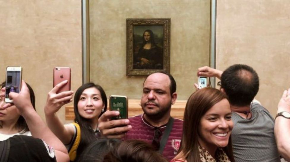 People taking selfies in front of a Painting of Mona Lisa
