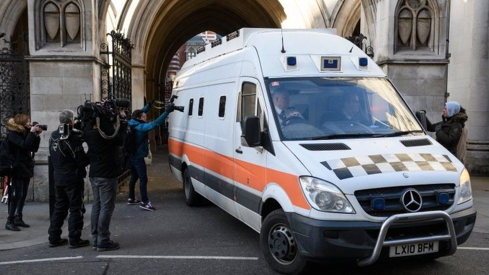 Members of the media look on as a prison van carries convicted rapist John Worboys from the High Court