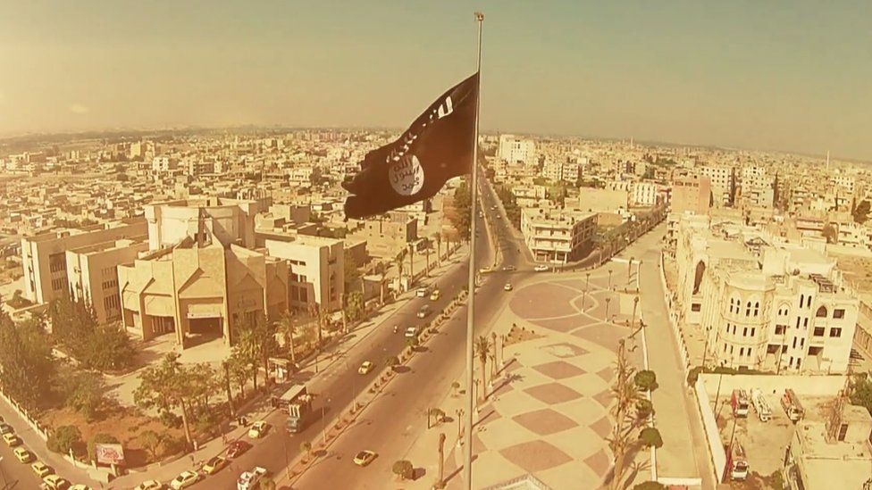 Screengrab of IS propaganda showing unidentified city with IS flag flying over it.