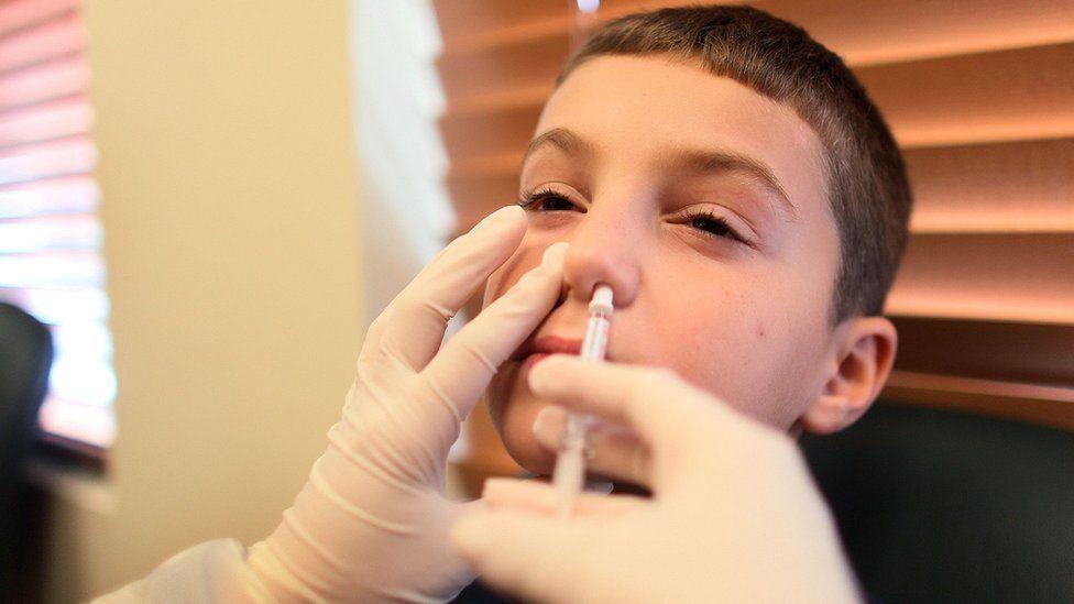 A young boy getting a nasal flu spray vaccine