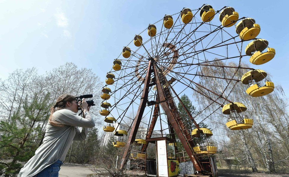 A woman films a Ferris wheel in the ghost city of Pripyat near Chernobyl