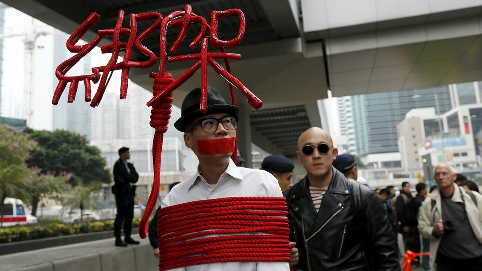 A protester ties himself in rope in a protest over the disappearance of Hong Kong booksellers