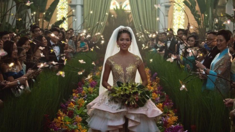 Movie still from Crazy Rich Asians showing Sonoya Mizuno walking down the aisle in a wedding dress