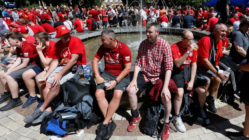 Liverpool fans sit around a fountain