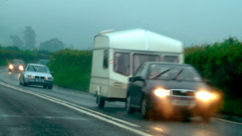 Driver towing caravan in rain