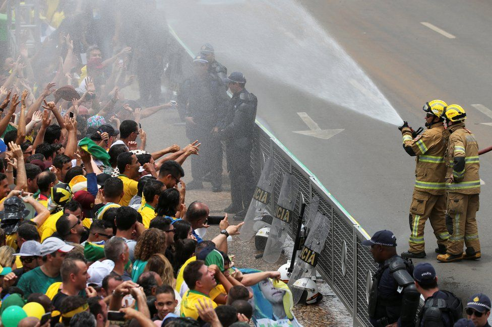 Firefighters spray water on supporters of Jair Bolsonaro outside the Planalto Palace, 1 January