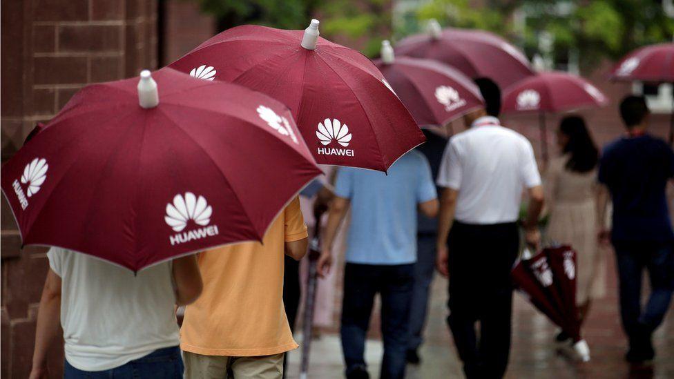 People holding Huawei umbrellas