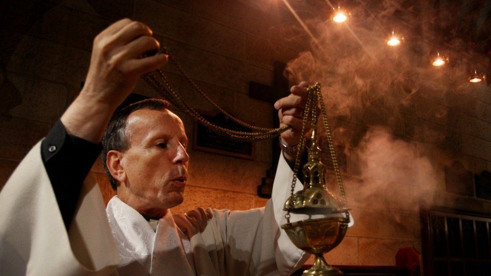 Anglican clergyman prepares thurible at church in Burwood, New South Wales, Australia
