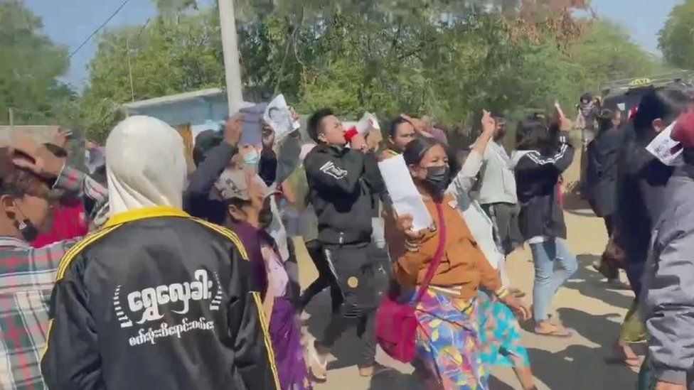 People chant as they march along a street during a protest against the military coup in Mandalay, Myanmar February 9, 2021, in this still image obtained from a social media video.