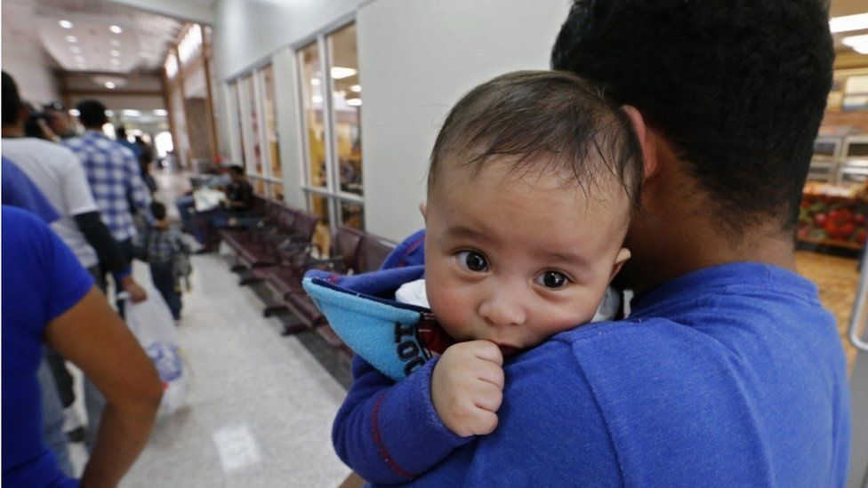A migrant with an infant waiting in line
