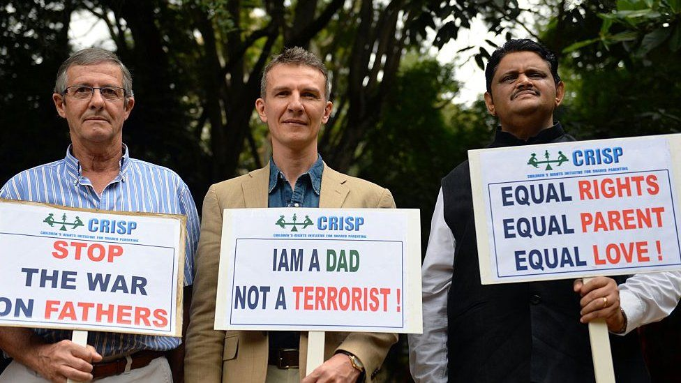 Pascal Mazurier (C), an ex-French consular officer who once worked for the French Consulate in Bangalore, holds a placard along with his father Jack Mazurier (L) after a press conference in Bangalore on June 17, 2015.