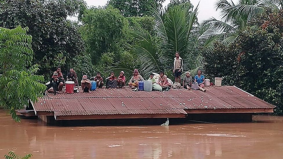 Lao villagers are stranded on the roof of a house after a dam collapsed in Attapeu province, Laos, 24 July 2018