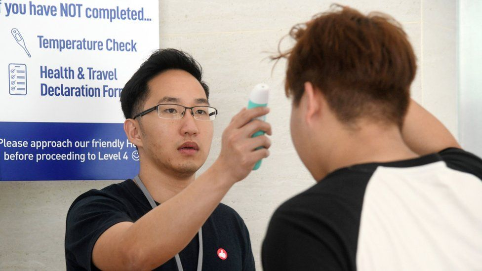 A volunteer (L) taking a temperature of a church member attending a small group service as a protective measure to prevent the spread of the COVID-19 coronavirus at the Heart of God church in Singapore.