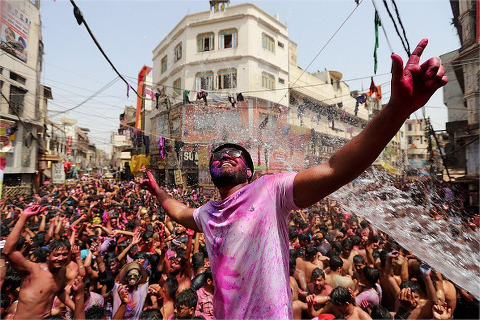 People dance as they throw coloured powder and spray water during Holi celebrations, amid the COVID-19 pandemic, in Prayagraj, India's northern state of Uttar Pradesh on March 30, 2021.