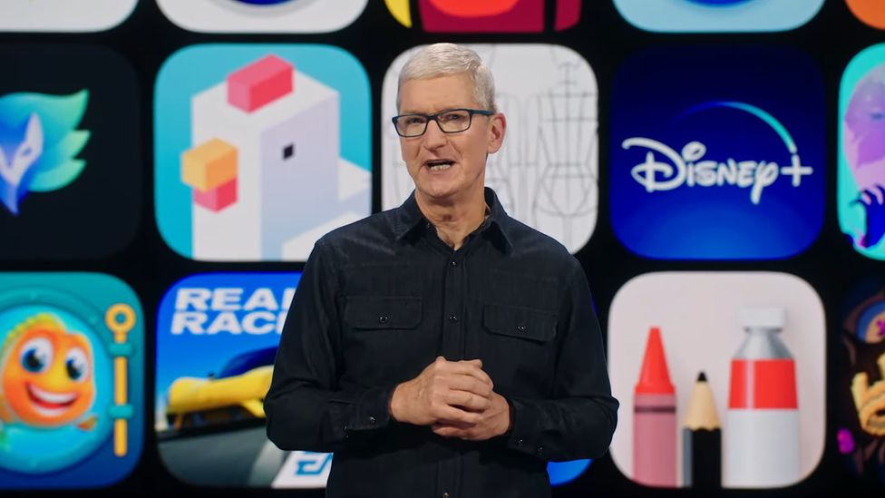 Tim Cook stands in front of a grid of app images on stage