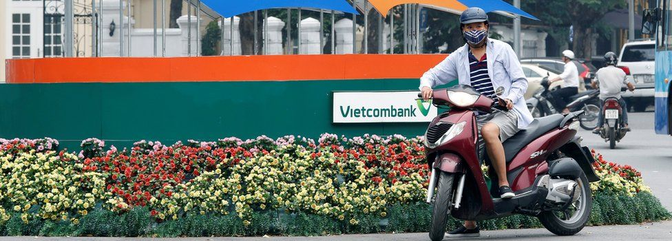 A motorbike waits in front of a sign promoting APEC Summit in Hanoi, Vietnam May 17, 2017