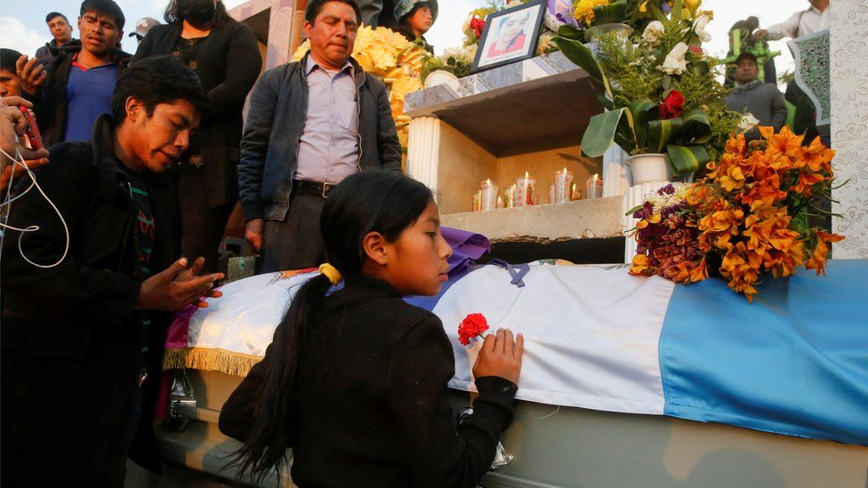 A girls holds a flower in front of the coffin with the body of a migrant killed in the Mexican state of Tamaulipas while trying to reach the US in January