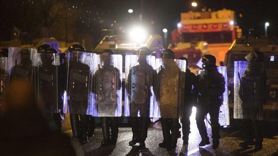 Police are seen during clashes with nationalist youths on the Springfield Road in west Belfast, in Northern Ireland
