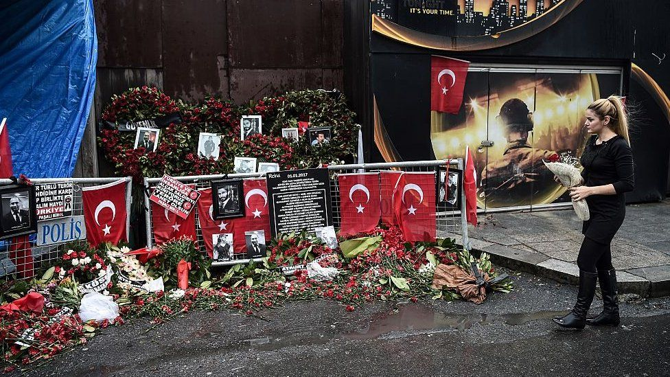 A woman lays flowers by a makeshift memorial in front of the Reina nightclub in Istanbul