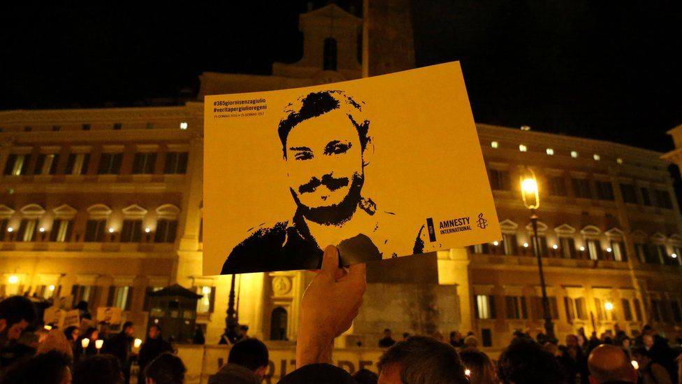 A sign with Regeni's face being held up at a demonstration