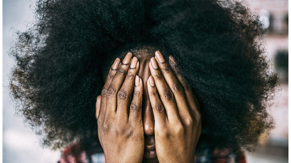A black woman covers her face with her hands