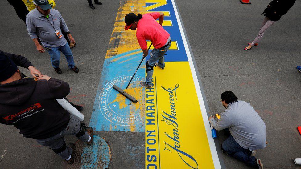 Crews install the decal marking the finish line on Boylston Street, for the 121st running of the Boston Marathon, in Boston, Massachusetts, U.S., April 13, 2017.
